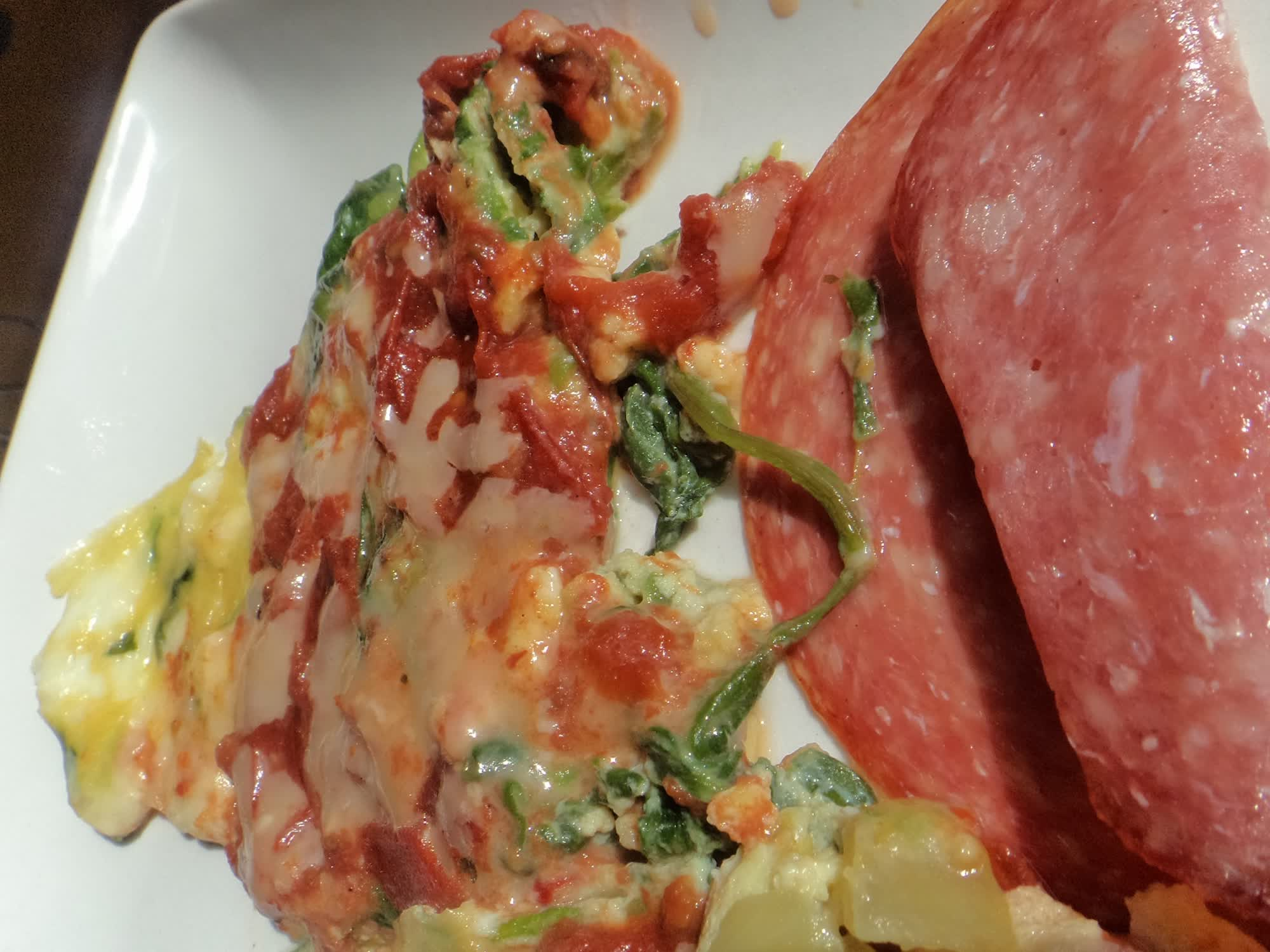 Tomato and cheese covered asparagus with salami.